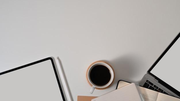 Draufsicht des arbeitsbereichs mit tablette, laptop, kaffeetasse, briefpapier und kopierraum auf weißem tisch