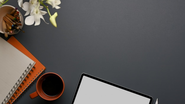 Draufsicht des arbeitsbereichs mit tablette, notizbüchern, kaffeetasse, kopierraum und blume verziert auf dem tisch