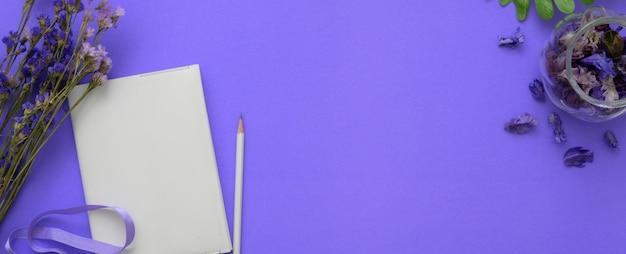 Draufsicht des arbeitsbereichs mit tagebuchnotizbuch, bleistift, blumen und kopienraum auf lila tisch