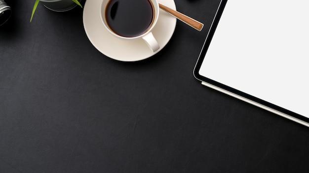Draufsicht des arbeitsplatzes mit digitalem tablett, kaffeetasse und kopierraum