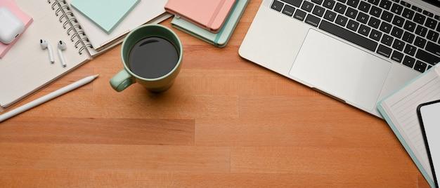 Draufsicht des arbeitsplatzes mit laptop, kaffeetasse, briefpapier und kopierraum im arbeitszimmer zu hause