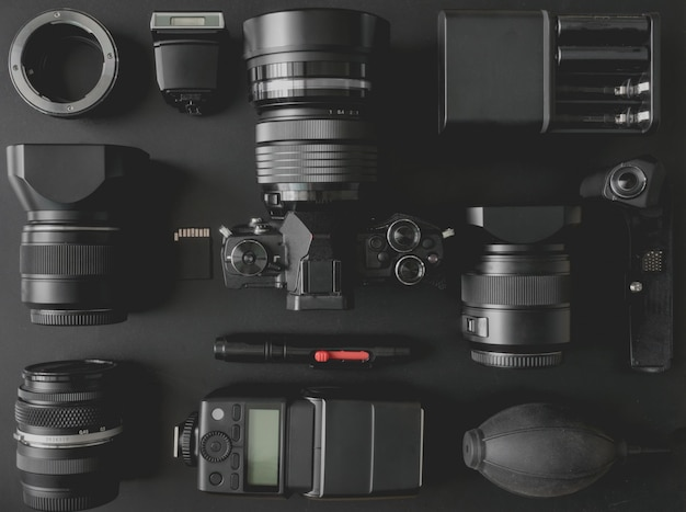 Draufsicht des arbeitsraumfotografen mit spiegellosem kamerasystem, kamerablitz, batterieladegerät, kamerareinigungssatz, speicherkarte und kamerazubehör auf schwarzem tischhintergrund