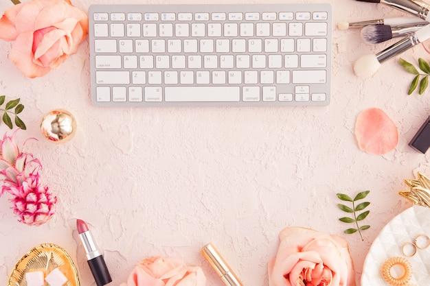 Draufsicht des arbeitsschreibtischs des frauenschönheits-bloggers mit computertastatur und laptop, dekorativer kosmetik, blumen und palmblättern