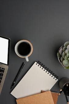 Draufsicht des arbeitstisches mit kaffeetassendekorationen des laptop-briefpapiers und kopierraum im hauptbüro