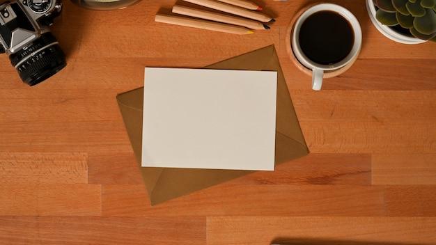 Draufsicht des arbeitstisches mit modellkarte, umschlag, briefpapier und kaffeetasse im hauptbüro