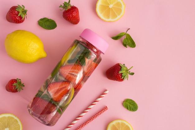 Draufsicht des aufgegossenen wassers mit erdbeere und zitrone in der flasche