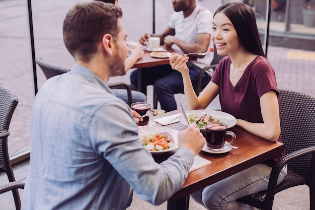 Draufsicht des aufrichtigen jungen glücklichen paares, das an café und frau aufwirft, die salat während des grinsens essen