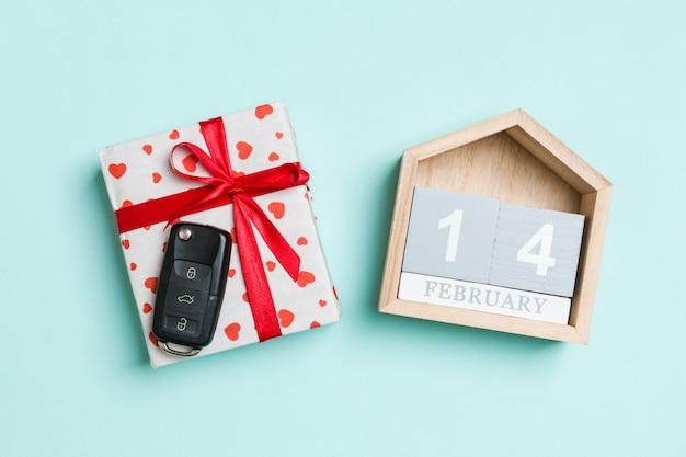 Draufsicht des autoschlüssels auf einer geschenkbox mit roten herzen und festlichem kalender auf buntem. 14. februar. geschenk zum valentinstag