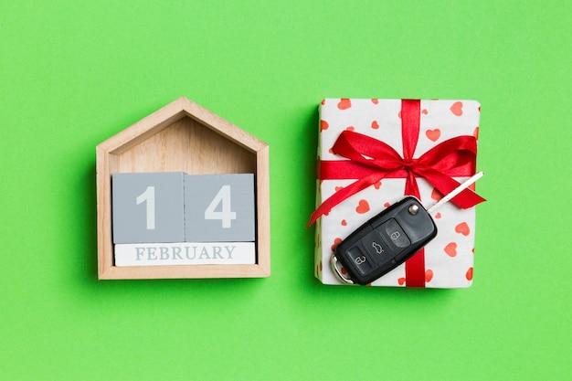 Draufsicht des autoschlüssels auf einer geschenkbox mit roten herzen und festlichem kalender auf buntem hintergrund. 14. februar. geschenk zum valentinstag-konzept