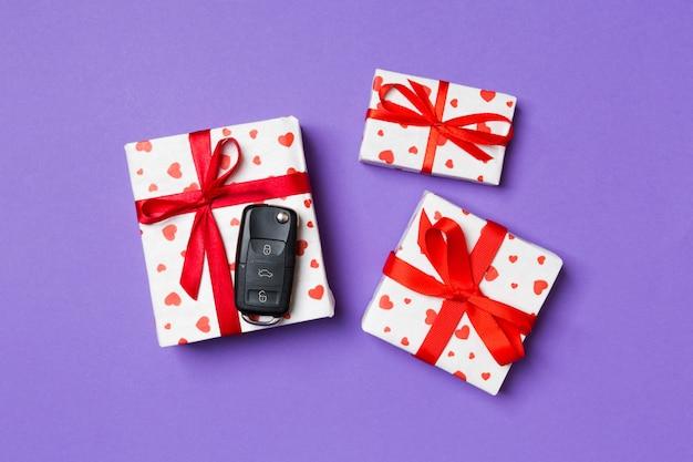 Draufsicht des autoschlüssels auf geschenkbox mit roten herzen