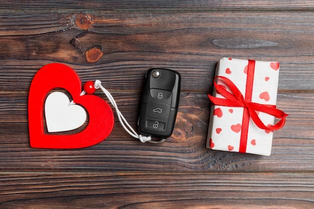 Draufsicht des autoschlüssels, der geschenkbox und des herzens als geschenk für valentinstag