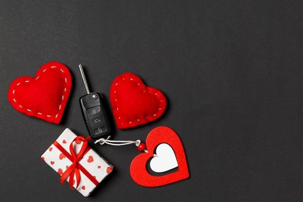 Draufsicht des autoschlüssels, der geschenkboxen und der spielzeugherzen