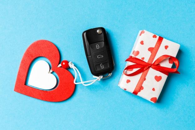 Draufsicht des autoschlüssels, der geschenkboxen und des spielzeugherzens auf blau