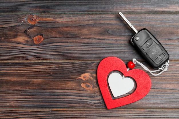 Draufsicht des autoschlüssels und des herzens auf hölzernem hintergrund