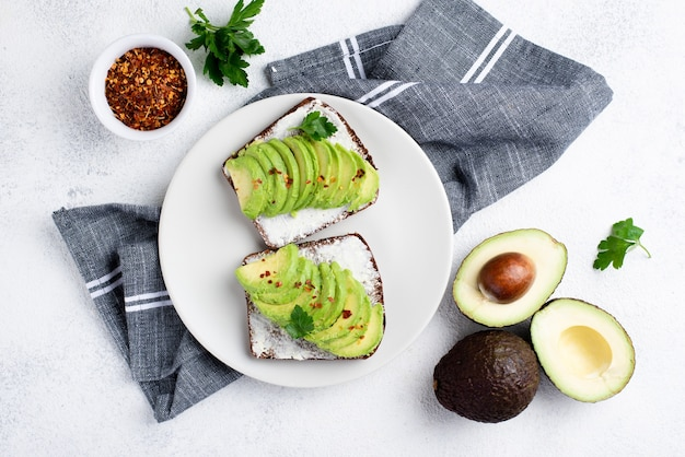 Draufsicht des avocadotoasts auf platte mit kräutern und gewürzen