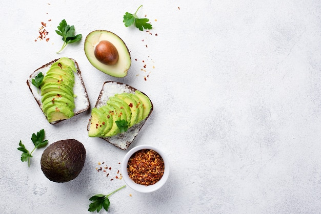 Draufsicht des avocadotoasts zum frühstück mit kräutern und gewürzen