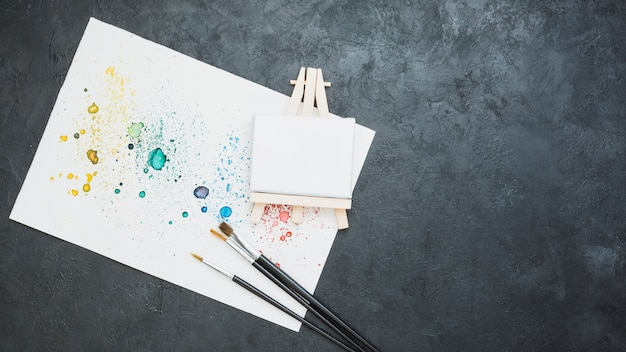 Draufsicht des befleckten gezogenen papiers mit pinsel und leerem mini gestell