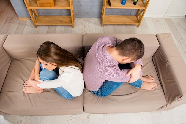 Draufsicht des benachteiligten mannes und der frau, die rücken an rücken auf dem sofa sitzen