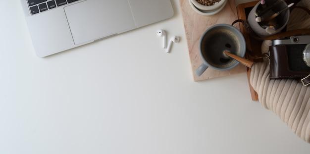 Draufsicht des bequemen arbeitsplatzes mit laptop-computer und büroartikel auf weißem schreibtischhintergrund