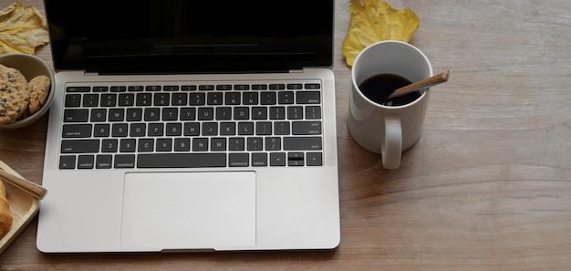 Draufsicht des bequemen arbeitsplatzes mit laptop-computer und kaffeetasse auf holztisch