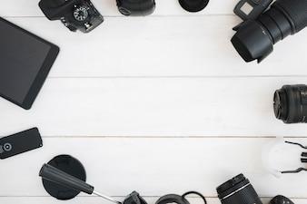 Draufsicht des Berufsphotographiezubehörs auf weißem Holztisch