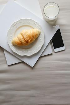 Draufsicht des betts mit hörnchen, glas milch, büchern und smartphone. frühstück im bettkonzept. konzentriert sich auf croissant.