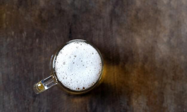 Draufsicht des bieres im glas auf dem holztischhintergrund
