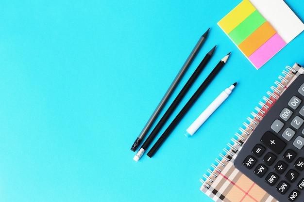 Draufsicht des blauen schreibtischs mit bleistiften, taschenrechner und notizbuch. zurück zum schulkonzept.