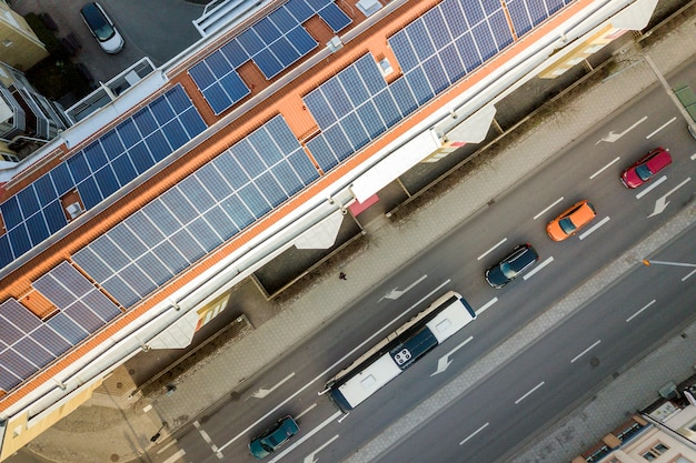 Draufsicht des blauen solarfoto voltaic panelsystems auf die hohe wohngebäudedachoberseite am sonnigen tag.