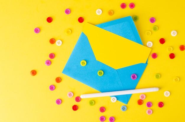 Draufsicht des blauen umschlags, der gelben leeren karte, des stiftes und der bunten knöpfe.