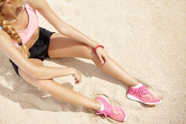 Draufsicht des blonden kaukasischen athletenmädchens mit dem langen zopf, der auf sandstrand sitzt, der arme auf knien ruht, sich nach langem laufen am meer am sonnigen tag entspannend, für marathon vorbereitet.