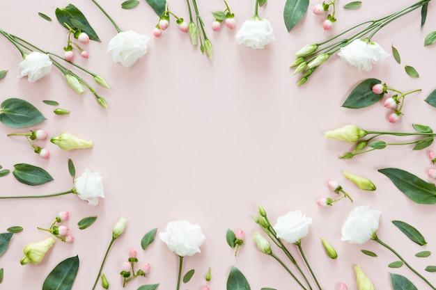 Draufsicht des blumenmusters der rosa und beige knospen, der grünblätter, der niederlassungen und der beeren auf rosa hintergrund mit kopienraum. flachgelegt, draufsicht. blumen textur