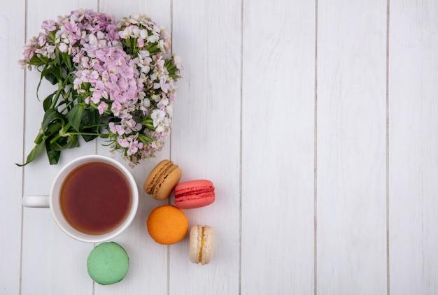 Draufsicht des blumenstraußes mit einer tasse tee und farbigen macarons auf einer weißen oberfläche