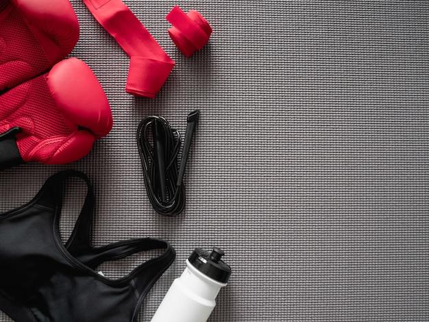 Draufsicht des box-turnhalle-konzepts mit boxhandschuh, fitness-studio-outfit, springseil und zubehör auf yogamattenhintergrund.