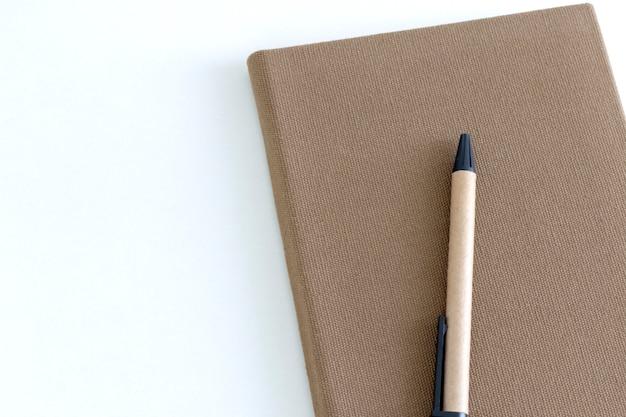 Draufsicht des braunen notizbuches und des stiftes auf weißem schreibtischhintergrund