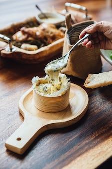 Draufsicht des brie-käse auf hölzernem brett auf holztisch.
