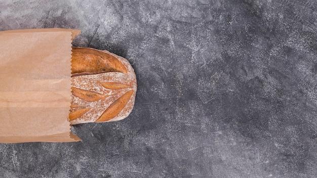 Draufsicht des brotes innerhalb der braunen papiertüte auf schwarzem strukturiertem hintergrund