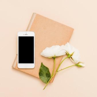 Draufsicht des buches, des smartphone und der blumen
