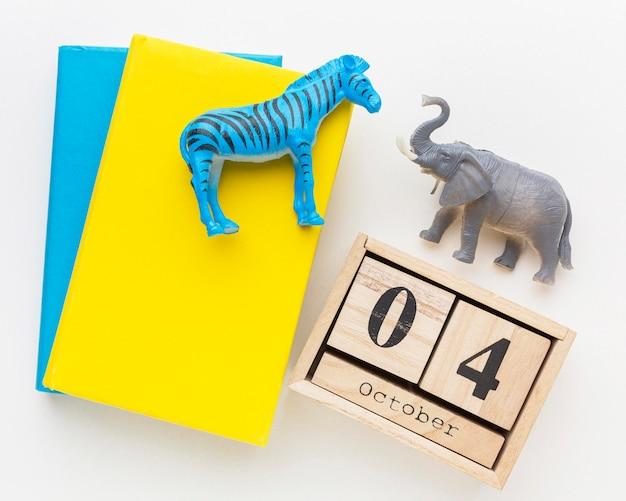 Draufsicht des buches und des hölzernen kalenders mit tierfiguren für tiertag