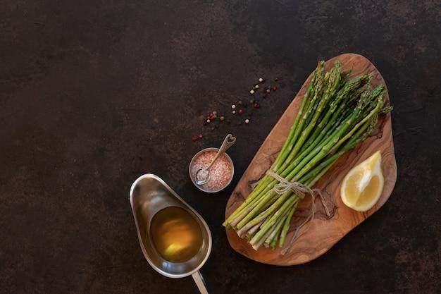 Draufsicht des bündels frischem grünem spargel mit zitrone, olivenöl und knoblauch auf tabelle