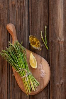 Draufsicht des bündels frischem grünem spargel mit zitrone und olivenöl auf holztisch