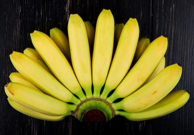 Draufsicht des bündels von bananen lokalisiert auf schwarzem holz