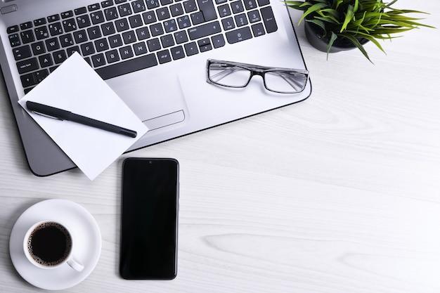 Draufsicht des büroarbeitsplatzes, hölzerner schreibtischtisch mit laptopnotizbuch, tastatur, stift, brille, telefon, notizbuch und tasse kaffee. mit kopienraum flach legen.