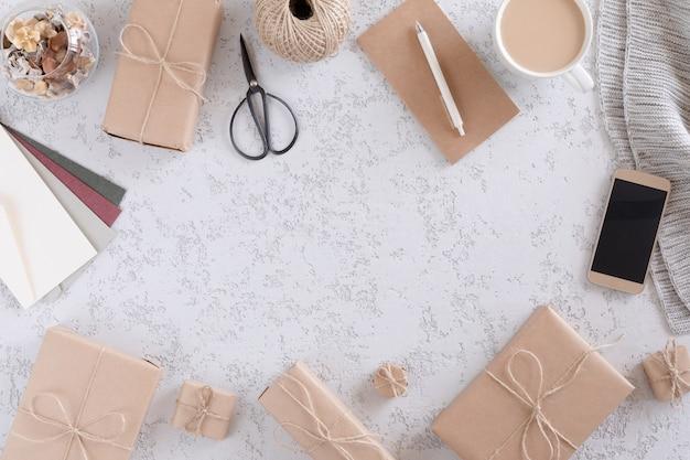 Draufsicht des bürobriefpapiers und des zubehörs, des handys, der geschenkboxen, des umschlags und der schale lattekaffees. minimalistic-ebenenlage, weinlese redete innenministeriumschreibtischarbeitsplatz an