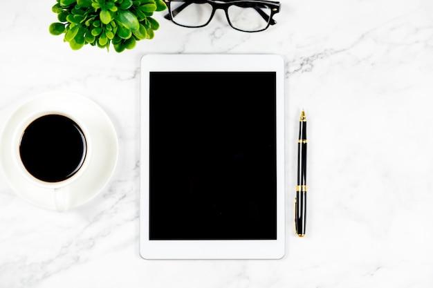 Draufsicht des büros, weißer marmorschreibtisch mit kaffee, gläser, tablette, stiftgeschäftskonzept.