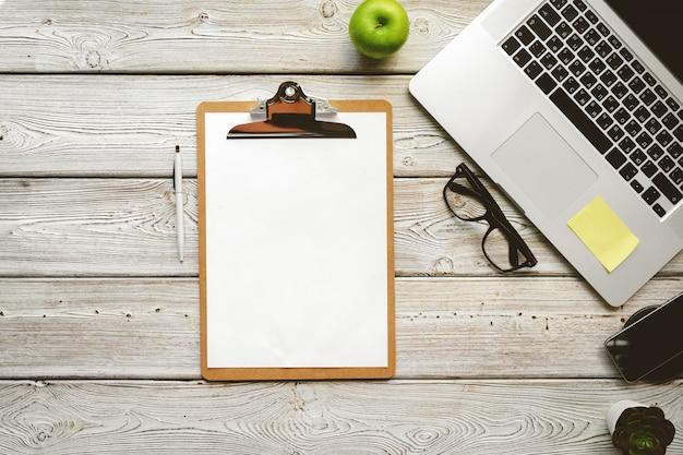 Draufsicht des bürotischarbeitsplatzes. hölzerner schreibtisch mit laptop, geräten und anlage