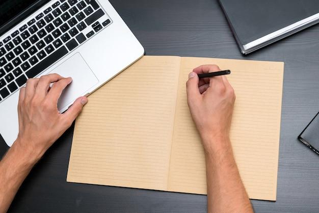 Draufsicht des bürotisches mit den händen des mannes, die mit stift auf leerem weinleseheft schreiben