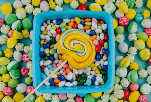 Draufsicht des bunten lutschers auf bonbons im mehrfarbigen glasurhintergrund