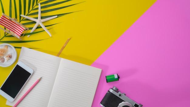 Draufsicht des bunten sommerarbeitsplatzes mit offenem notizbuch, smartphone und kamera auf rosa und gelbem schreibtisch