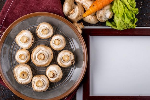 Draufsicht des champignons der frischen pilze auf keramikplatte auf dem tisch